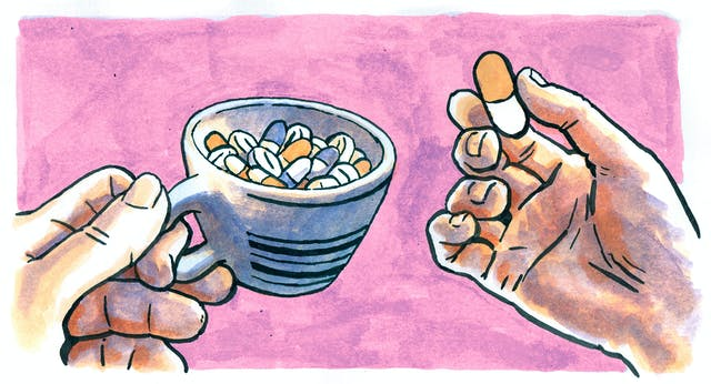 Hands holding a coffee cup filled with pills