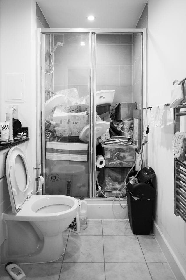Black and white photograph of a bathroom shower cubicle which is full of objects and being used as a storage area rather than a shower.