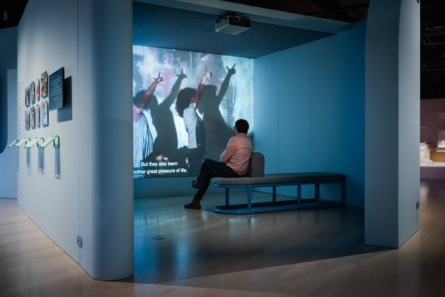 Photograph of a man sitting on a bench in an exhibition space watching a projected film. The film still shows 2 children with their hands in the air casting a shadow on the wall behind. The subtitle on the film reads,