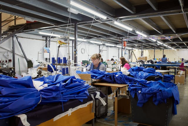 Photograph of a series of workstations within a clothing manufacturing workshop. There is a woman at the centre of the image working at a sewing machine. She is surrounded my blue medical fabric at various stages of construction.