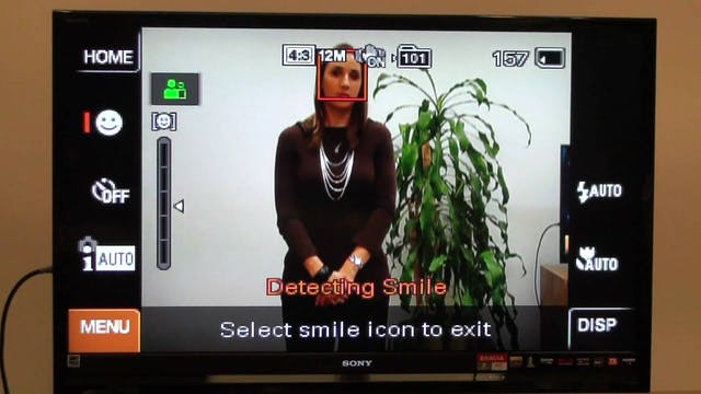 "A screengrab from a YouTube video demonstrating the interface from a Sony Cybershot camera. On the camera screen a woman stands beside a plant and the camera screen reads ""Detecting Smile""."