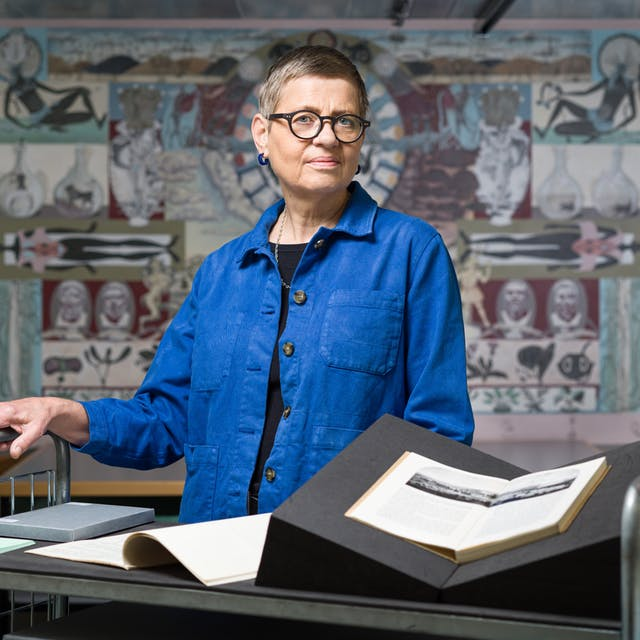 Photograph of a woman wearing a blue shirt standing behind a trolley in an archive store. One the trolley are open books and archive boxes. On either side of her are a series of thin drawers. In the background on the wall is a painted mural depicting various figures.