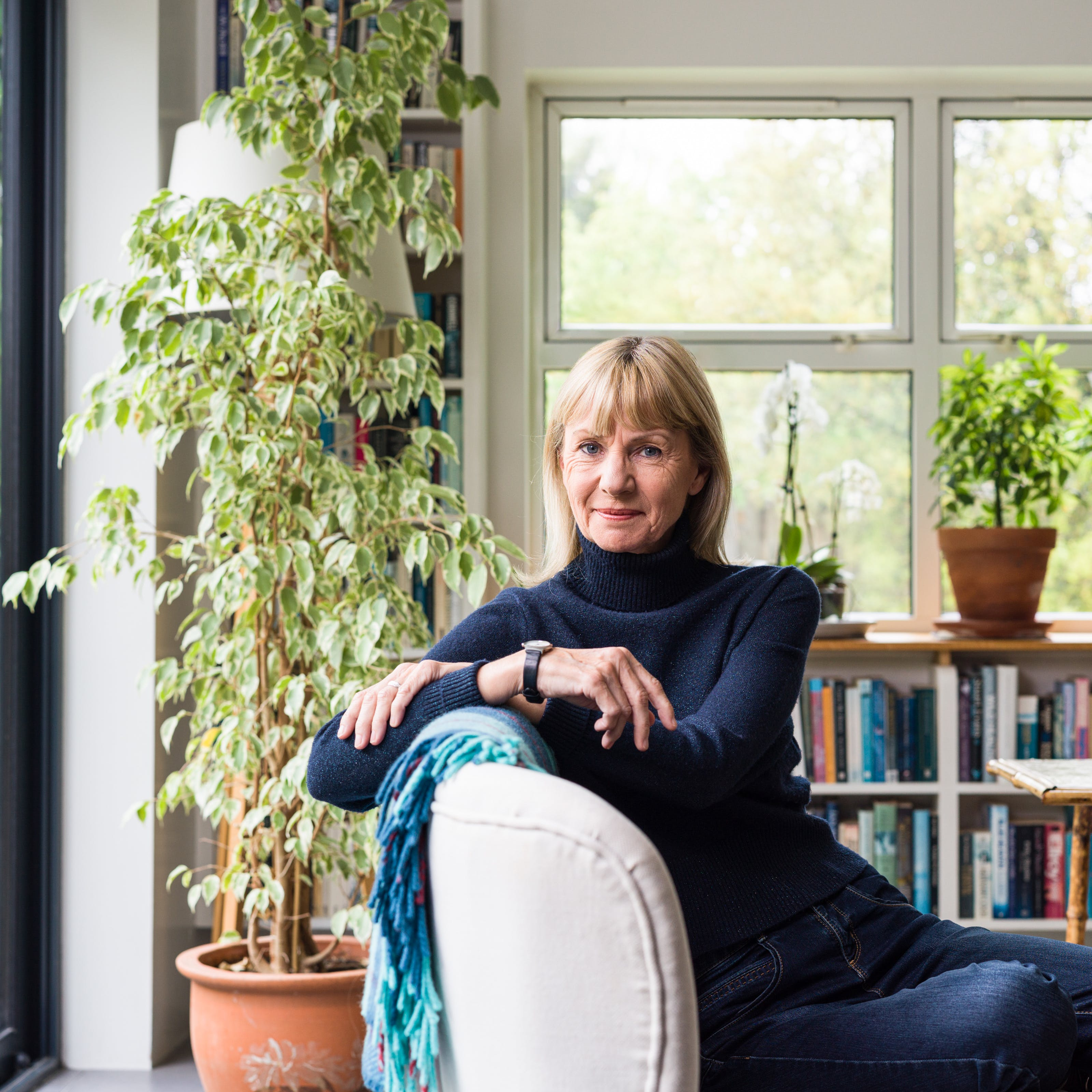 A photographic portrait of a woman with blonde hair wearing a navy turtleneck jumper and blue jeans. She is leaning to the left over the back of a sofa and in the background are a number of houseplants and shelves full of books.
