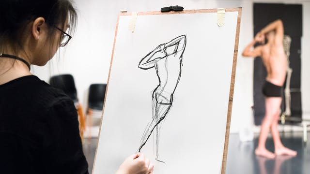 Photograph of a life drawing workshop showing an young woman sketching at a charcoal drawing of a male figure who can be seen posing in the background.