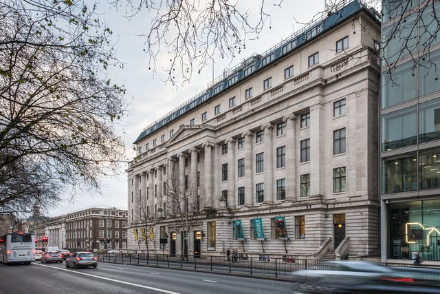 A photograph showing the front of the Wellcome Collection building, a grand building built in 1936, and Euston Road in front of it. The pale stone facade features 12 decorative columns, of which the four central columns support a triangular roof like decoration between the fourth and fifth floors. Six floors are visible, and each floor has fifteen windows, except the ground floor where there are three doors at street level.