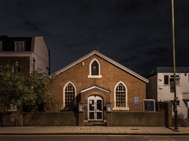 Photograph of Wimbledon Spiritualist Church at night.  The red brick Victorian building has white window recesses and a glass stained window bearing a cross in the apex of the facade.  The building is detached in a residential setting.