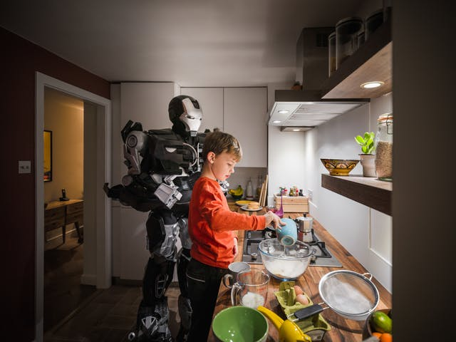 Photograph of a young boy standing at a kitchen countertop mixing the ingredients for pancakes. Behind him stands a large robot holding a spatular, ready to help make the pancakes.
