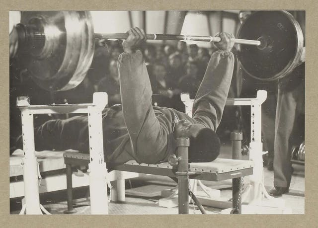 Black and white photographic print showing a black man on a weightlifting bench holding a large barbell above him with straight arms and clenched fists. A leg of a spotter or observer is just visible to the right, and behind the barbell and the weightlifter are an audience whose blurred faces lean forward, focusing on the competitor.