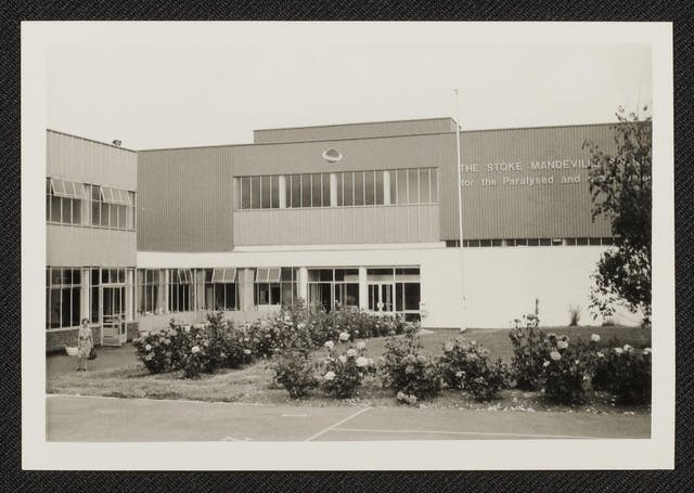 Black and white photographic print of Stoke Mandeville Hospital, showing a boxy concrete building with lots of rectangular windows. There are rose bushes in front of the building and a woman in a dress holding a bag is standing on the path that leads towards the open glass double doors.