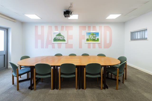 A photograph showing a white room containing a large table surrounded by chairs and a wall on which there is a large mural with the words 'have' and 'find' painted in large light pink capital letters. In the middle of the word 'have' is a smaller picture of a tree with the word 'strength' across it. In the middle of the word 'find' is a picture of a tree with the word 'peace' across it.