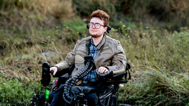 Photographic portrait of a young person seated outside in a electric wheelchair looking to camera. Behind them are long grasses and shrubs lit from behind by a low sun.