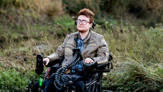 坐在看对照相机的电轮椅的一个年轻人的摄影画象。在他们身后是长的草,灌木从低阳光下点燃。