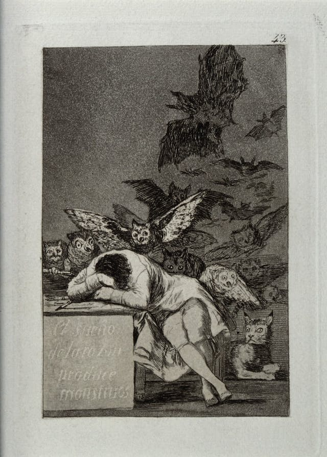 Black and white image of a seated man with his head in his arms, resting on a table. Owls and bats swarm behind him.