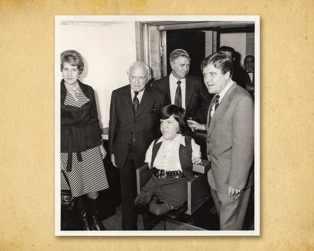 Photograph of a black and white photographic print, resting on a brown paper textured background. The print shows a young man seated in the centre of the image who has short arms and legs as a result of his mother being prescribed thalidomide during pregnancy. The young man is surrounded by a woman and three older men in suits and ties.