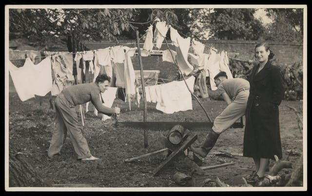 Black and white photograph showing tow men sawing a log in half, with a women in the foregound facing the camera, and washing lines in the background.