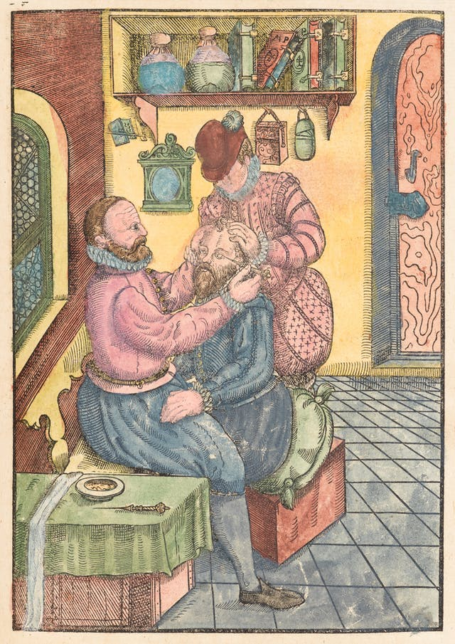 Coloured engraving in a 16th century manuscript showing a seated man having an eye operation. A man in front of him uses an piece of apparatus on the left eye of the seated man, whilst a man behind him holds his head still with his hands.