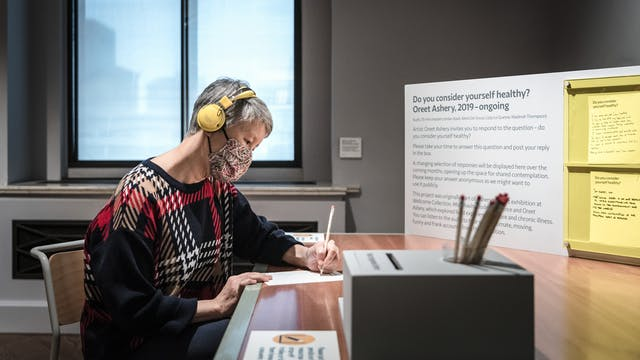 Photograph of an individual sat at a desk in a museum gallery setting, wearing a face covering and a pair of yellow on-ear headphones. They are holding a pencil in their left hand, writing on a sheet of paper. To their right is a small post box and a pencil holder. Behind them is a window. In front of them is a large information panel with the title,