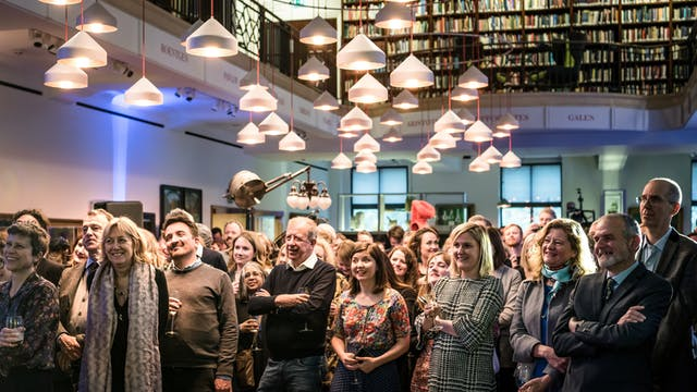 Photograph of an audience standing in the Reading Room at Wellcome Collection listening to a performance.