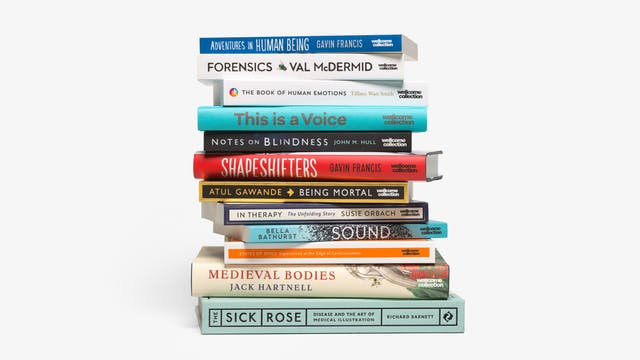 Photograph of a pile of 12 book stacked horizontally, one on top of the other. They are stacked in a somewhat higgledy piggledy manner. The spines range in colour from blue to red to black to light green. They have been photographed on a white background with a small grounding shadow.