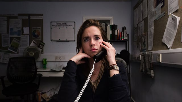Photograph of a woman sat in an office environment. She is holding a landline telephone receiver to her left ear and is looking into the distance over the top of the camera.