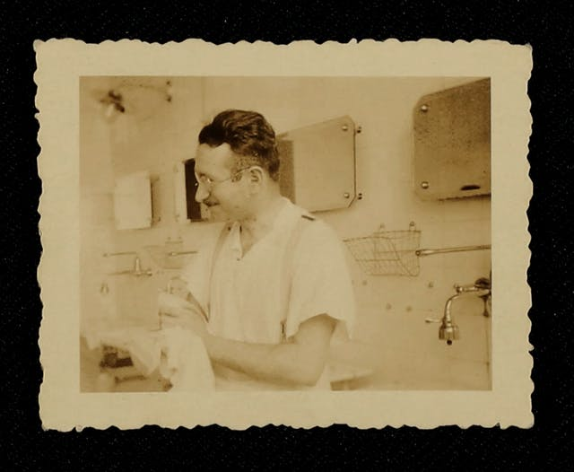 Sepia photographic print of Ludwig Guttmann in his medical practice in the 1930s. Guttmann has wavy dark hair, glasses and a moustache just above his top lip. He is wearing a white, short-sleeved shirt and braces. He is wiping his hands on a light coloured cloth and appears to be smiling and looking away to the left of the image. Behind Guttman are lots of wall-mounted mirrors, taps and baskets on a tiled wall.