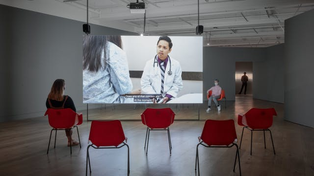 Photograph of a gallery space with grey walls and a wooden floor. Hung from the ceiling is a large screen, onto which a video is projected. the video shows a man in a white coat with a stethoscope around his neck talking to someone whose back can be seen to the left of the video. Subtitles can be seen on the screen. In the foreground and background are red plastic chairs. One person is sitting facing the screen, another is sitting facing the camera. Both are wearing face coverings.