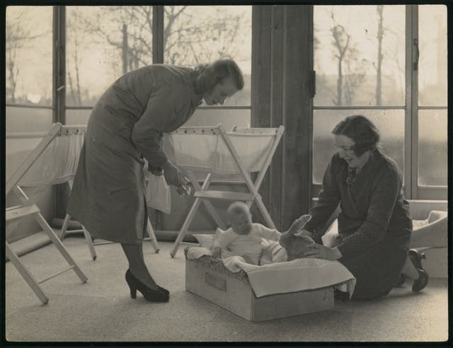 Black and white photograph showing two women attending a baby in a cot.