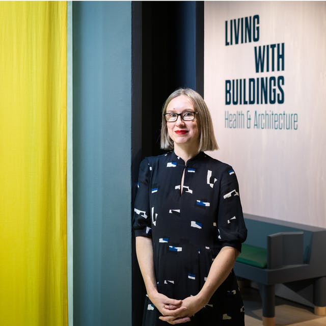 Photographic portrait of Emily Sargent, curator of the exhibition Living with Buildings at Wellcome Collection. Emily is leaning against a pillar within the exhibition space, with a hanging yellow drape to the left and the title of the exhibition to the right.