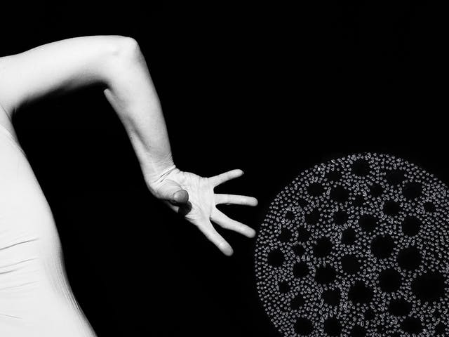 Artwork made up of a black and white photograph of part of a female figure from behind, from the waist up, against a black background. Her body is twisted in a dancerly pose.  Her right arm is bent down to the ground, hand outstretched. To the right and below her right hand is another large circular shape with holes in the middle, made up of a layered texture of grey dots which are painted onto the print creating a three dimensional texture.