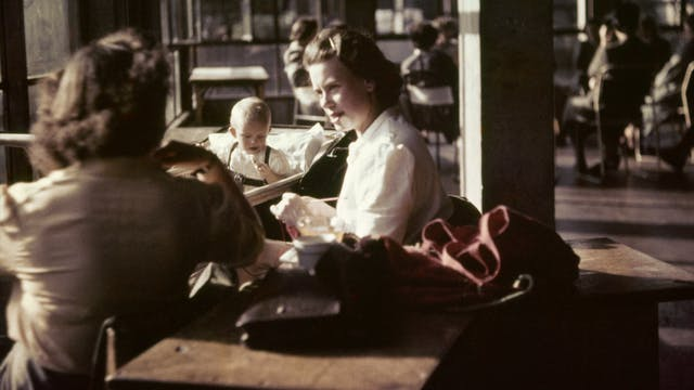 Photograph from the mid-20th Century Peckham Pioneer Centre, showing two women seated at a table, speaking, whilst a baby plays in a pram behind them and in the distance another group sit at tables. The building in which they sit has concrete columns and large windows.