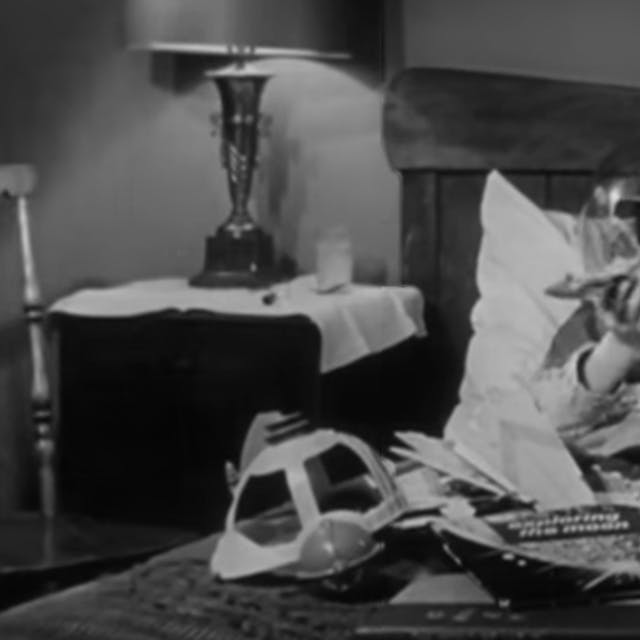 Black and white still from a film showing a boy in a bed wearing a space helmet and playing with a model spacecraft, with other space-themed toys and comics on his lap.