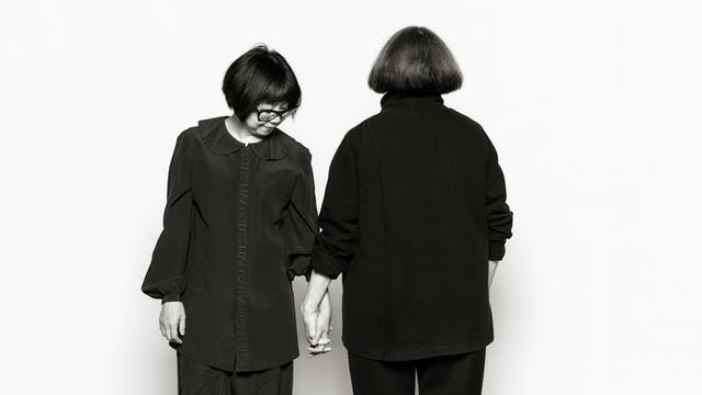 Photographic portrait of two women holding hands. One is facing away from the camera , the other is looking at their clasped hands.