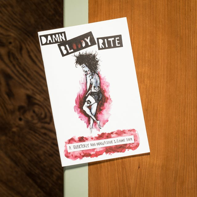 Photograph of Damn Bloody Rite zine on a library desk