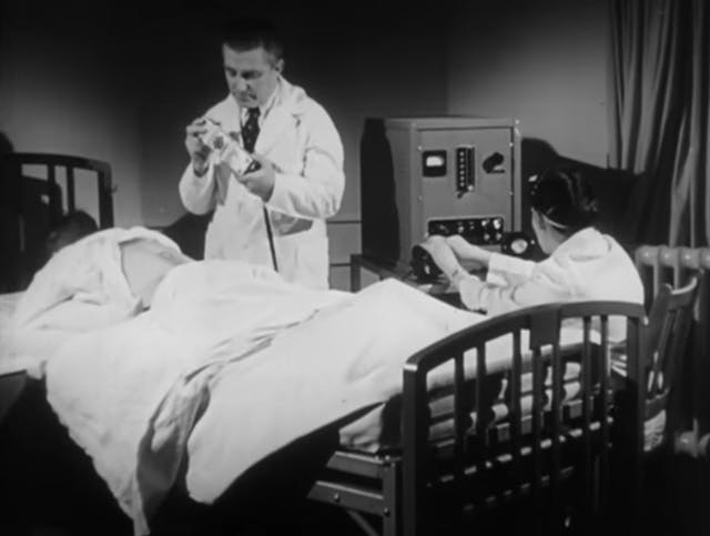 Image of a patient lying on his stomach in bed with his shirt lifted to expose his back. A man wearing a lab coat stands over him and a woman wearing a lab coat operates a box-like machine next to the bed.