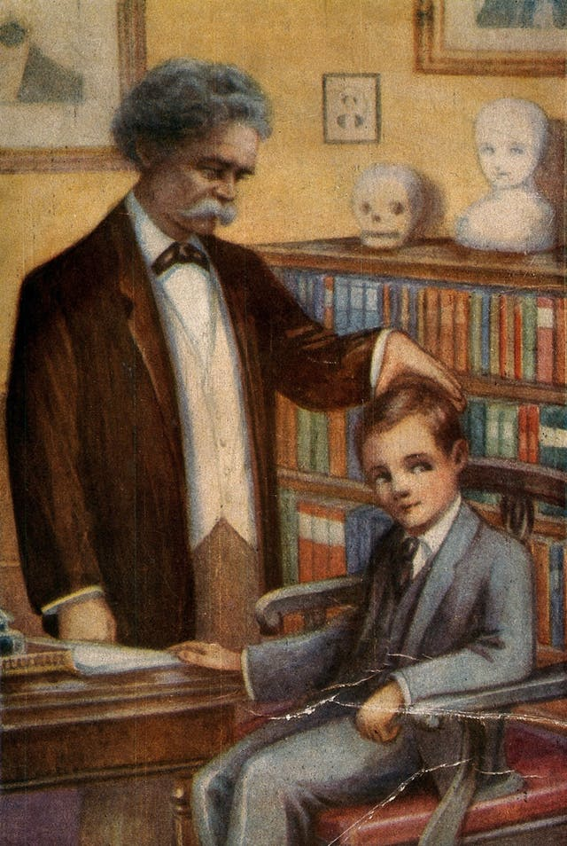 Colour image of a man standing up and a boy sitting down in a study. The man is touching the boy's head, as if to gauge its width.