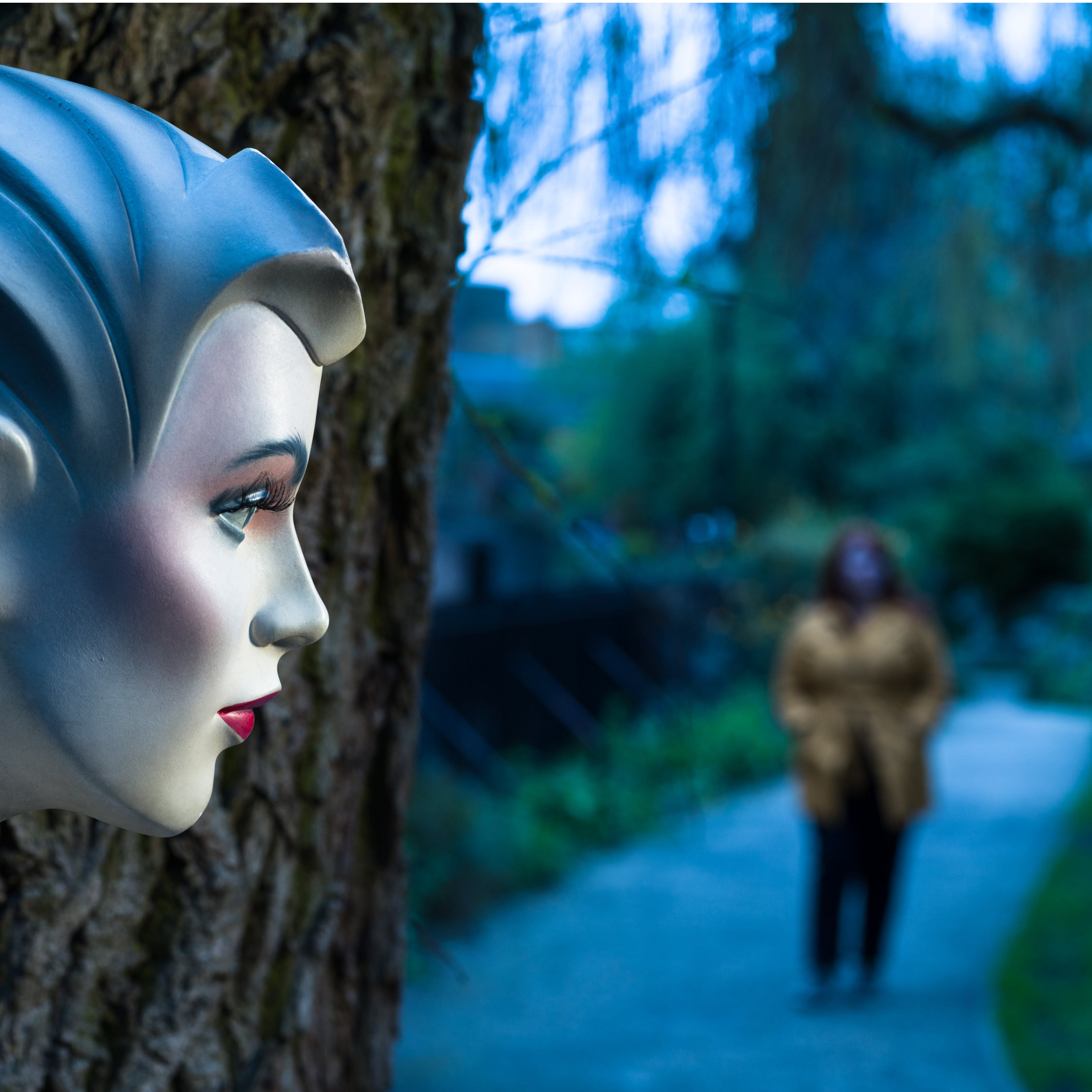 Photograph of the profile of a mannequin's head in front of a tree trunk. In the background an out-of-focus young woman approaches.