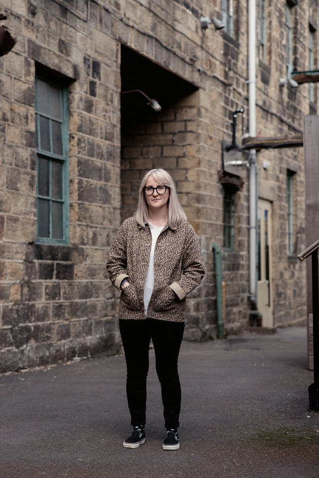 Photograph of a young woman with shoulder length blond hair and glasses in full length. She is standing in an industrial back-street location, wearing a white t-shirt, a leopard skin patterned jacket and black leggings. Her hands are in her jacket pockets and she is looking to camera with a slight smile. Behind her in the background is a large brick building with windows and doorways and external pipework and cables.