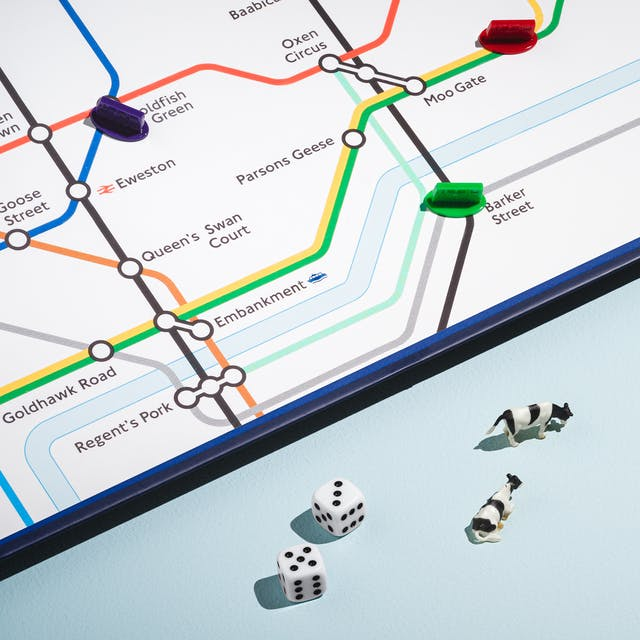 A photograph of a bottom right section of a board game featuring a city underground map with animal place names such as Moo Gate, Ham Heath and Oxen Circus is visible in the top left of the frame. In the bottom section are two die with the numbers five and three, 5 toy cows and a toy London Underground Carriage.