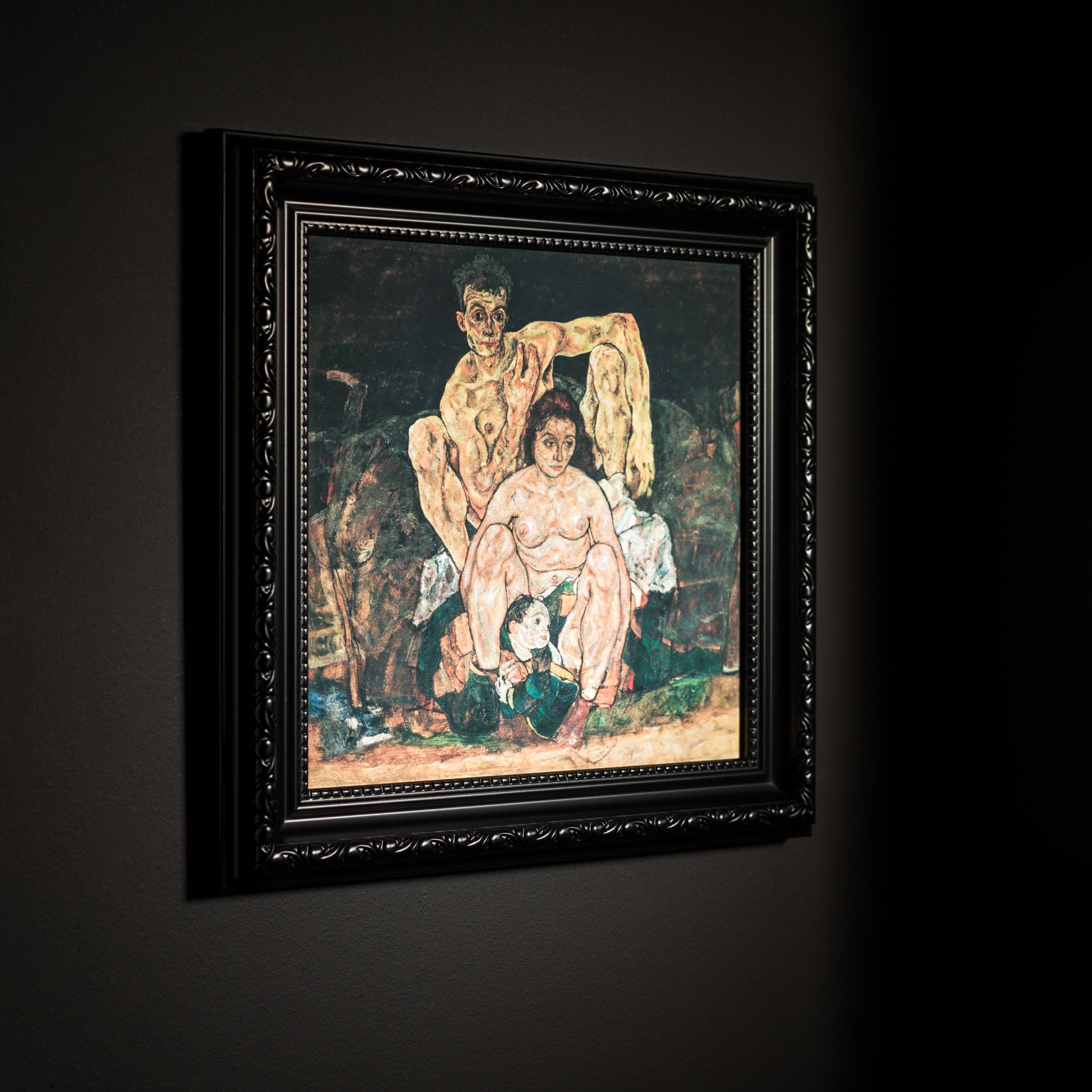 Photograph black ornate picture frame hung on a black wall. Inside the frame is a print of an oil painting by Egon Schiele titled, 'The Family'. It depicts  Schiele himself at the far back, his sinewy nude body hunched behind his wife, Edith, who looks off to the side, while a child is curled between her feet.