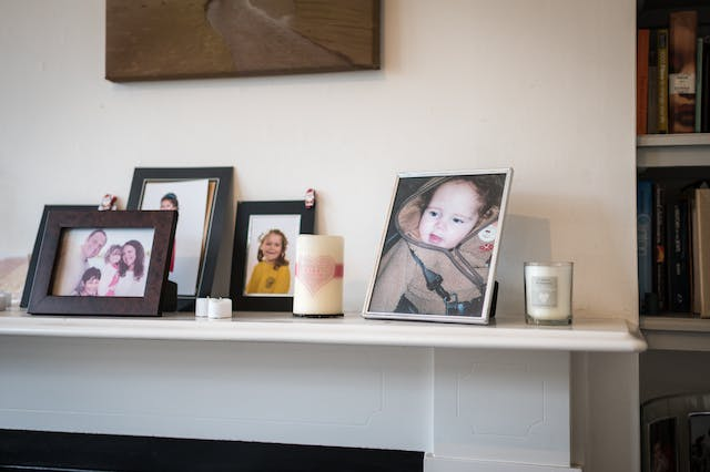 Photograph showing a mantlepiece with a collection of family photos in frames. The largest frame shows a baby in a fleece top.