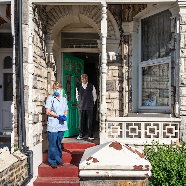 Photograph of the front of a house showing the front door, front window and some of the garden. A man stands in the open front doorway. A few steps down from him stands a woman in a nurses uniform wearing blue latex gloves and a blue face mask.