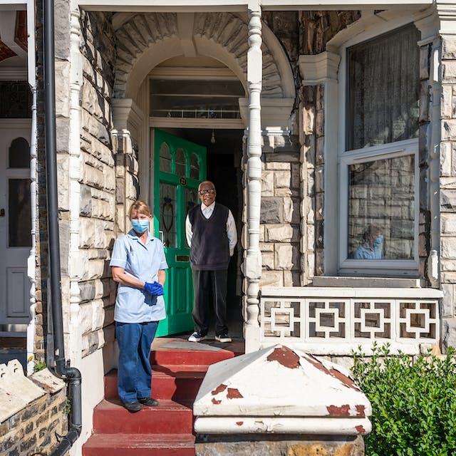 一张房子前面的照片,展示了前门、前窗和一些花园。一个男人站在敞开的前门。离他几步远的地方站着一个穿着护士制服的女人,戴着蓝色乳胶手套和蓝色口罩。