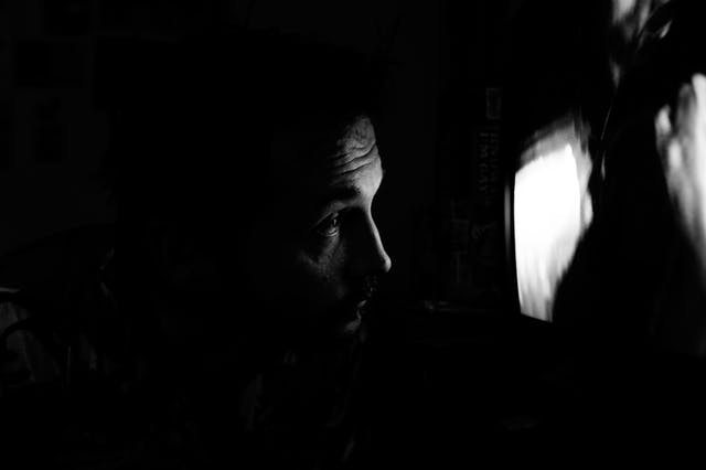Black and white photograph showing a dark room with a tv screen. The light from the tv screen illuminated the profile of a man