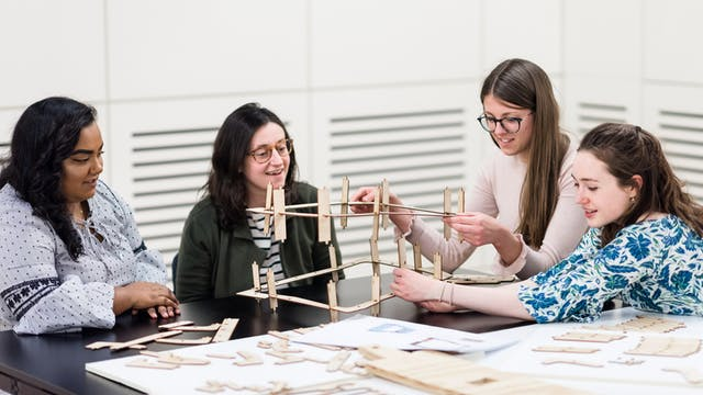 Photograph of four young women engaged in a practical workshop event in the Forum at Wellcome Collection.