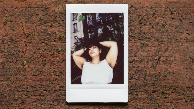 Photograph of an Instax Mini instant film print resting on a textured brick surface.  The print shows a woman against the branches and leaves of a tree outside a tall row of houses, with her arms raised up to show her armpit hair. She is wearing a white top.