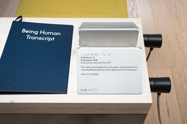 A photograph of the Being Human Transcript, blue with white text, and audio handsets relating to an audio performance titled