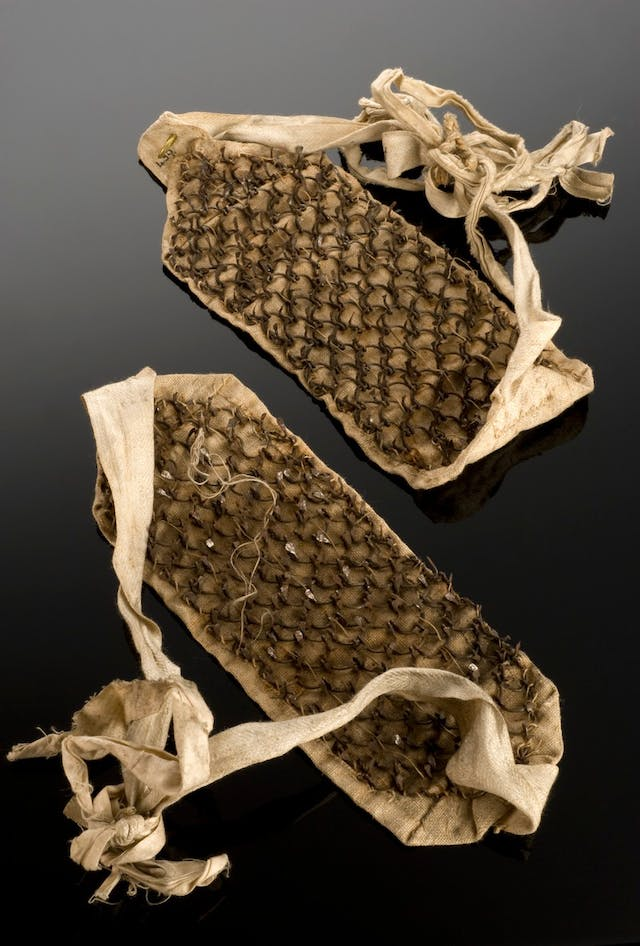 Image of brown rectangular patches of cloth with spikes on. Cloth bands attach at either end.