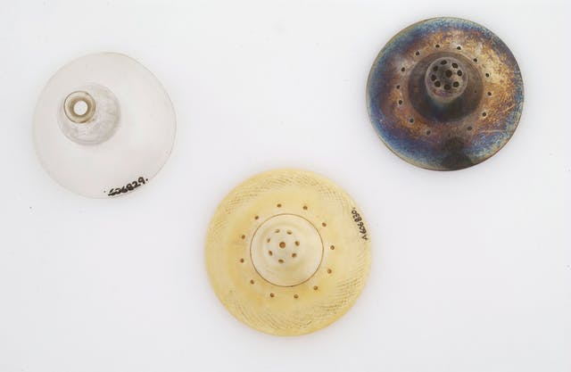 Colour photograph of three nipple shields (objects in the shape of nipples with holes in for feeding through). The one on the left is made of glass, the middle one is ivory, and the one on the right is made of silver.