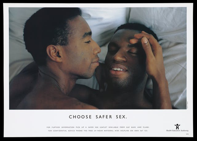 A photograph of two gay black men laying in bed with the headline
