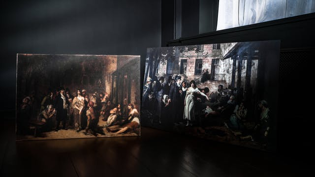 Photograph of two oil paintings propped against the walls in the corner of a dark room, on a wooden floor.  To the right is a recessed window with a white fabric curtain hanging in front of the glass.